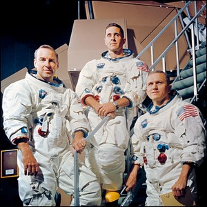 portrait photo of three American astronauts wearing spacesuits without helmets